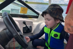 Little boy thinks he is driving the boat.