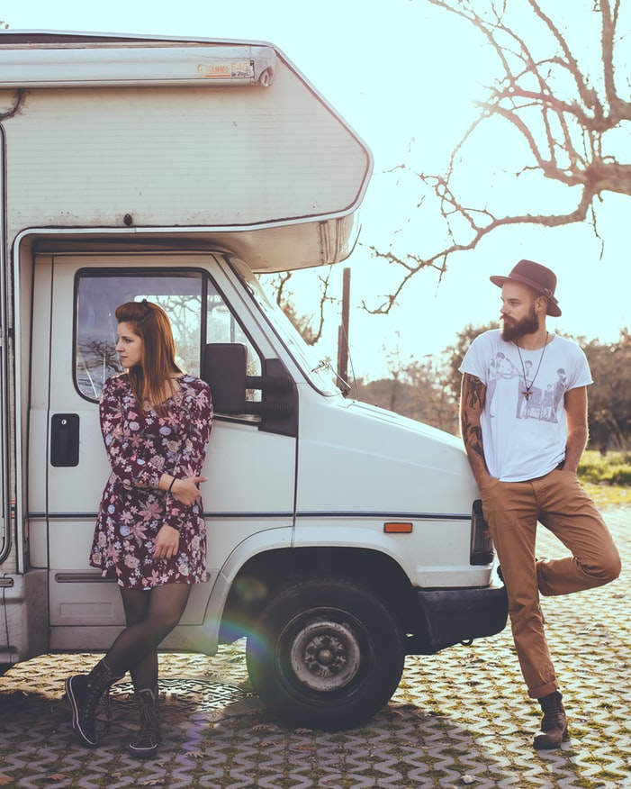 Young couple leaning up against their caravan