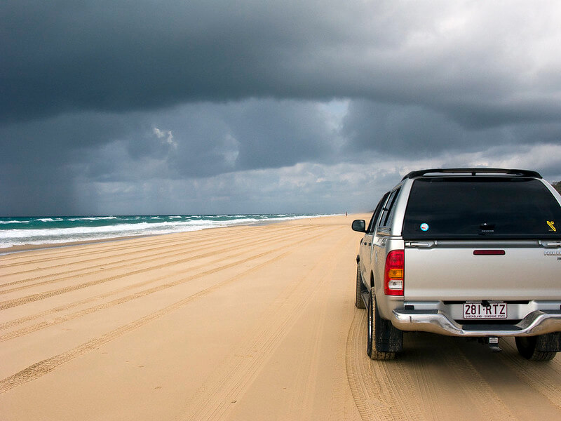 Silver 4wd driving across the beach as a storm rolls in