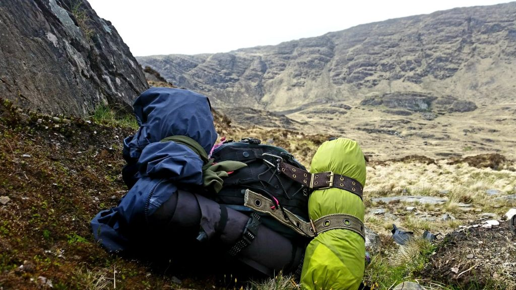 Green and black camping gear sat on a grassy hill
