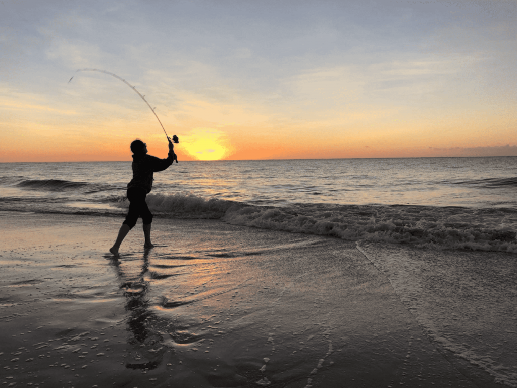 Silhouette of a person fishing at sunset