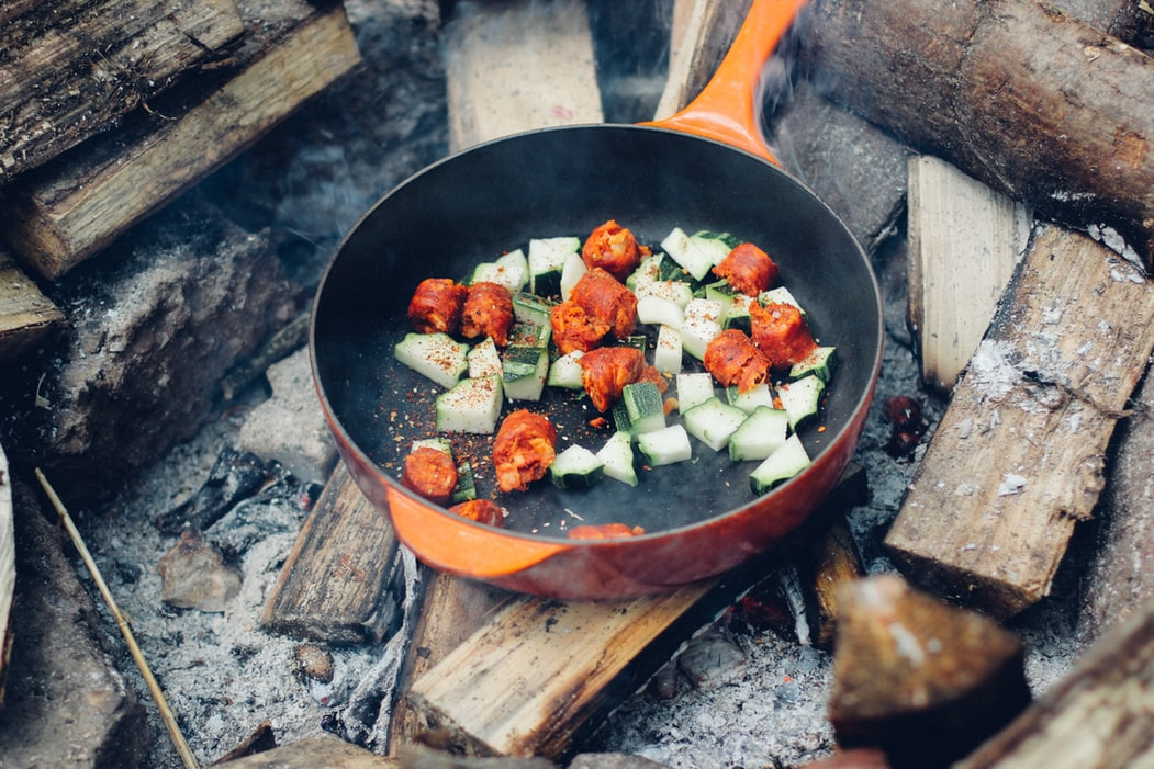 Cooking food on the coals of a campfire