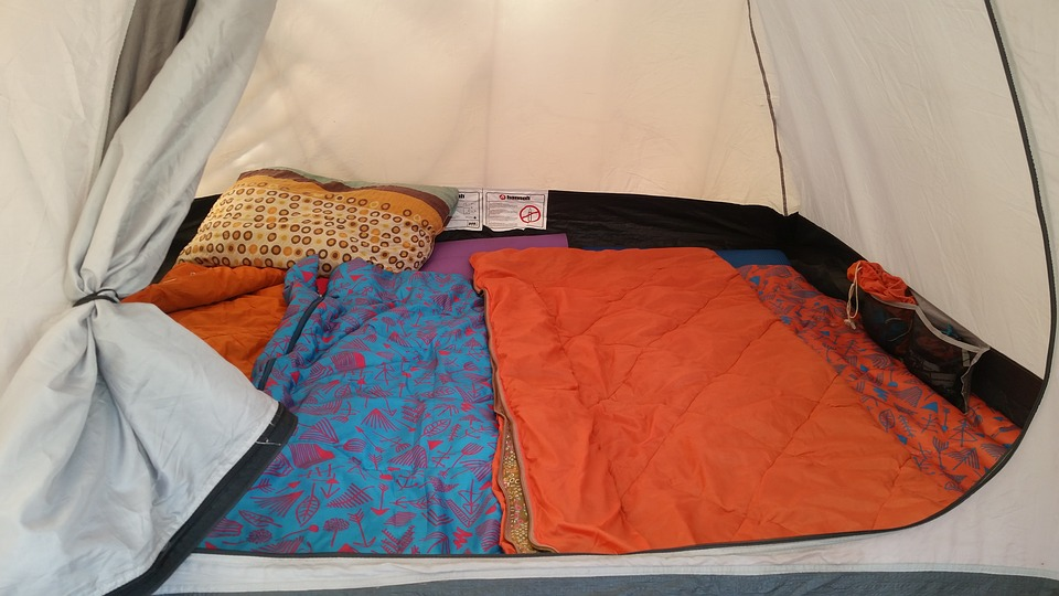 Tent lined with colourful sleeping mats and sleeping bags