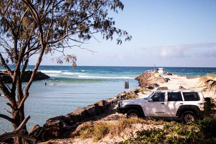White 4wd parked at a beach